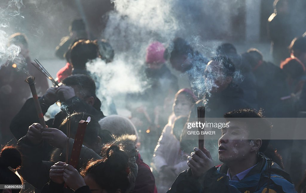 A man burns incense for good luck at the Yonghegong Lama Temple on the first day of the Lunar New Year in Beijing on February 8, 2016. Millions of Chinese began celebrating the 'Spring Festival', the most important holiday on the Chinese calendar, which this year marks the beginning of the Year of the Monkey. AFP PHOTO / GREG BAKER / AFP / GREG BAKER