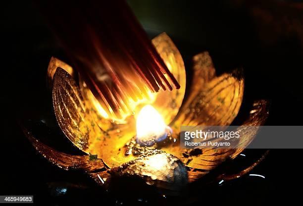 A man burns incense sticks as he prays at Hong San Ko Tee Temple during Chinese New year Celebrationson January 31 2014 in Surabaya Indonesia...