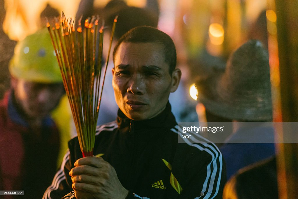 A man burns incense to pray for good luck and fortune at the Yuanmiao Taoist Temple on first day of new Year of Monkey on February 8, 2016 in Huizhou, Guangdong Province of China. Chinese people celebrate the Spring Festival for the new Year of Monkey, which fell on February 8 according to Chinese calendar.
