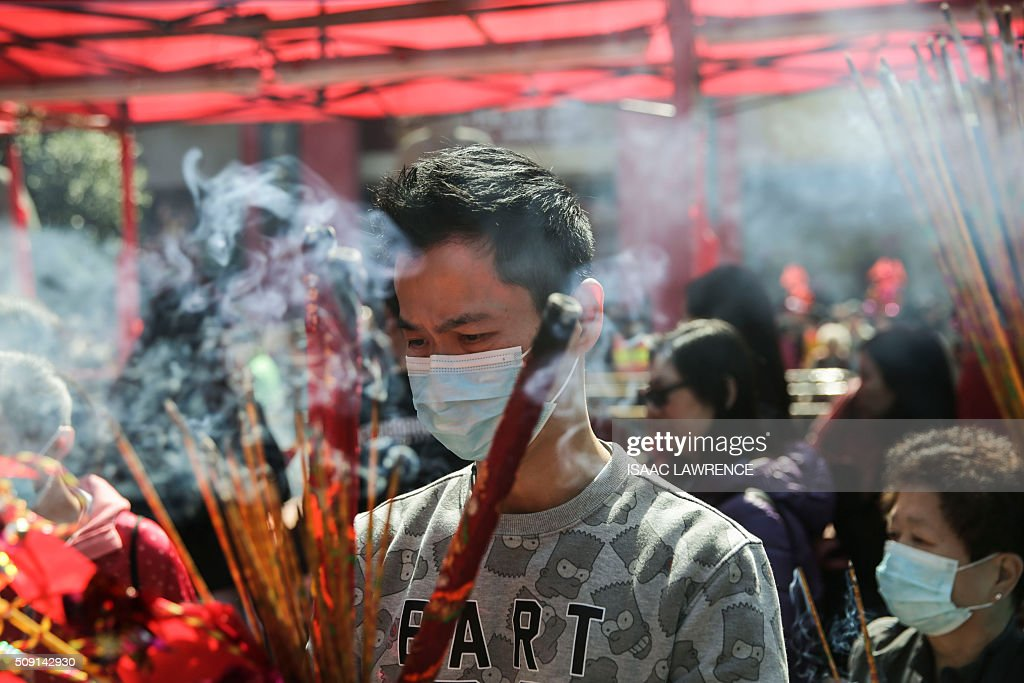 A man burns joss sticks as an offering during celebrations for the Lunar New Year at the Che Kung Temple in the Sha Tin district of Hong Kong on February 9, 2016. The Lunar New Year of the Monkey began on February 8. AFP PHOTO / ISAAC LAWRENCE / AFP / Isaac Lawrence