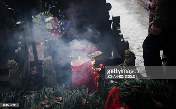 A man burns paper money during the annual 'Qingming' festival or Tomb Sweeping Day at a public cemetery in Shanghai on April 6 2015 During 'Qingming'...