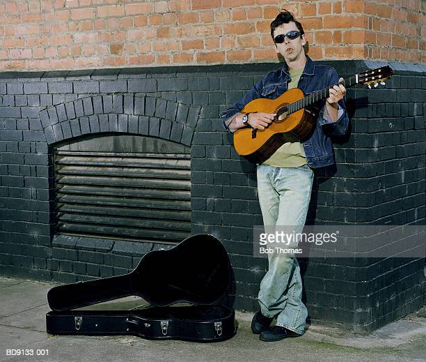 Man busking with acoustic guitar, leaning against wall