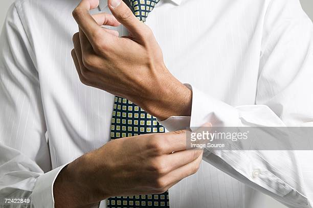 Man buttoning cuff of his shirt