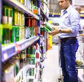 Man in supermarket buying beer.