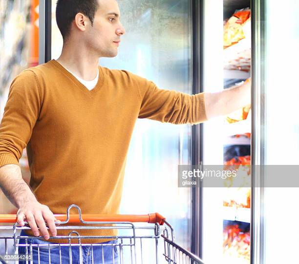 Man buying frozen food in supermarket.
