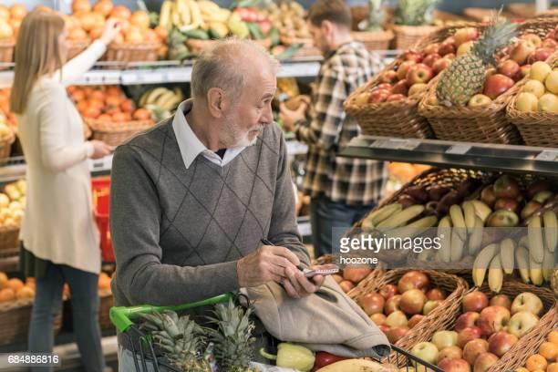 Homme acheter des fruits au supermarché