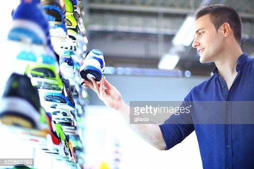 Homem Compra os sapatos de desporto.
