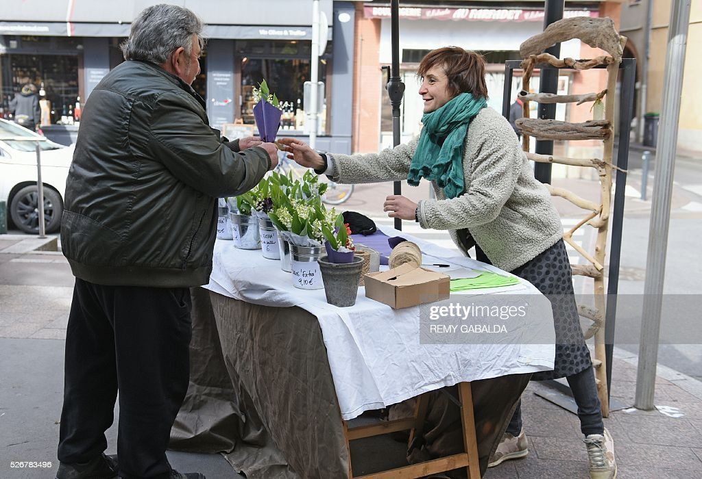 A man buys a bouquet of lily of the valley at Place des Carmes during May Day celebrations in Toulouse, southern France, on May 1, 2016. / AFP / REMY
