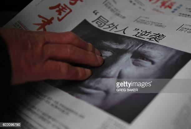 A man buys a Chinese newspaper with the headline that reads 'Outsider strikes back' featuring Donald Trump on the front page in Beijing on November...