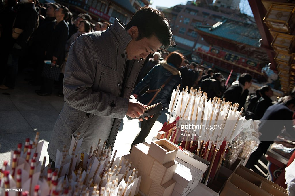 A man buys a decorative arrow - a charm for warding off bad luck - on the first day of business in 2013 at the Kanda Myojin shrine in Tokyo, Japan, on Friday, Jan. 4, 2013. Japan's deflation-plagued economy has contracted 7 percent since 2007 as six prime ministers, including Shinzo Abe in his first term, failed to reverse the course. Photographer: Noriko Hayashi/Bloomberg via Getty Images