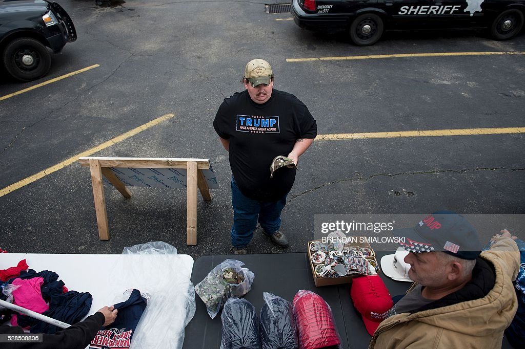 A man buys a hat before a rally for Republican US Presidential hopeful Donald Trump in Charleston, West Virginia on May 5, 2016. It's the paradox of the 2016 US presidential elections: Hillary Clinton and Donald Trump are virtually assured of facing off against each other in November, and yet both are widely unpopular. / AFP / Brendan Smialowski