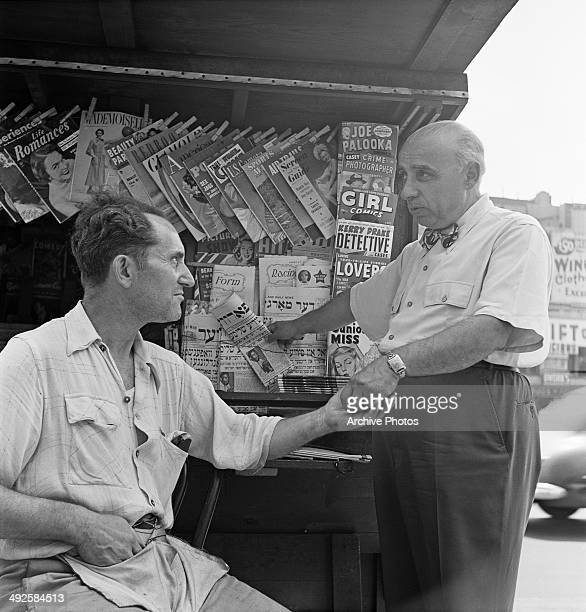 A man buys a Jewish newspaper from a kiosk on the Lower East Side of Manhattan New York City USA circa 1955