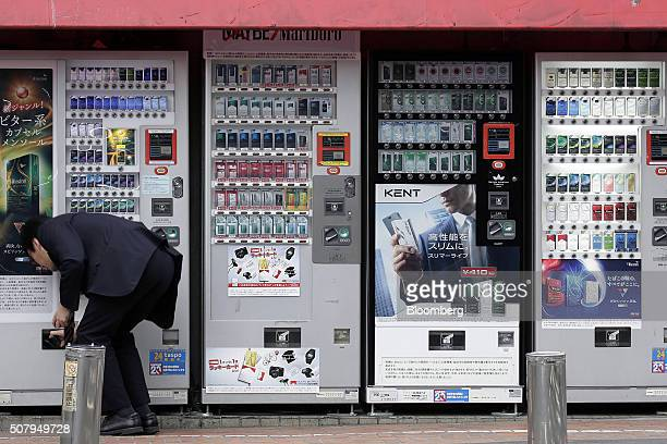 A man buys a packet of cigarettes from a vending machine selling Japan Tobacco Inc brands left in Tokyo Japan on Monday Feb 1 2016 Japan Tobacco is...