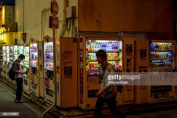 A man buys a product from a vending machine in Akihabara Electric Town on May 19 2014 in Tokyo Japan Akihabara gained the nickname Akihabara Electric...