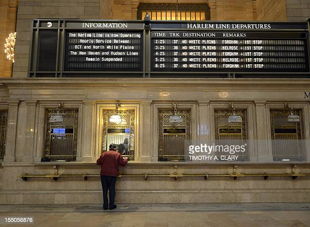 A man buys a ticket at the Metro North Railroad ticket windows as the MTA opens up since closing Sunday night for the first train out of the station...