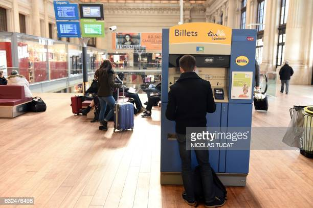 A man buys a ticket from a ticket machine at the Hall 1 of the Bordeaux train station on January 23 2017 in Bordeaux southwestern France following...