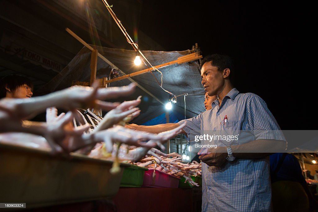 A man buys chicken at the Pasar Badung market in Denpasar, Bali, Indonesia, on Tuesday, Oct. 8, 2013. Bank Indonesia said it will regulate currency hedging by individuals and companies, including state-owned firms, to help stabilize Asias most-volatile currency. Photographer: SeongJoon Cho/Bloomberg via Getty Images