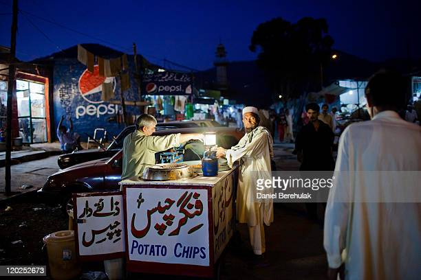 A man buys food from a street vendor after 'Iftar' when Muslims break their fast on the first day of the holy month of Ramadan on August 2 2011 in...