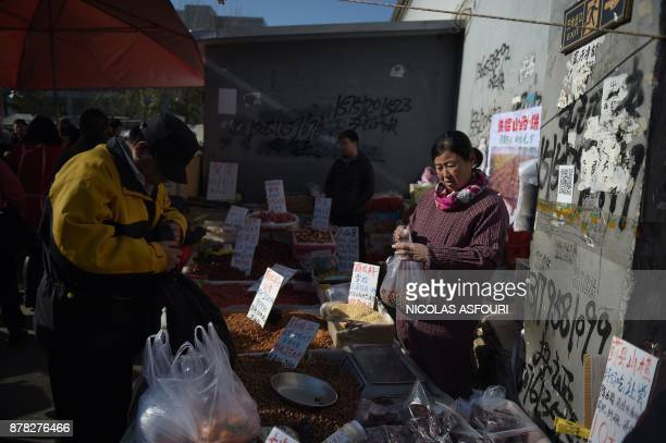 A man buys nuts at a market in Beijing on November 24 2017 / AFP PHOTO / NICOLAS ASFOURI