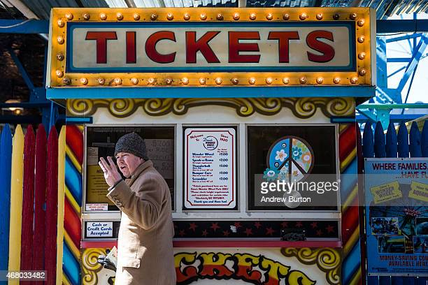 A man buys tickets for rides at Coney Island on March 29 2015 in New York City Various Coney Island businesses including Luna Park opened for the...