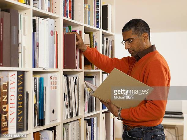 Man by bookshelf looking at book