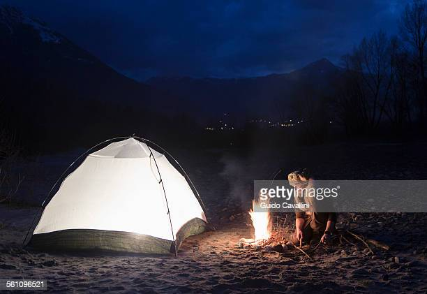 Man by campfire and tent at night