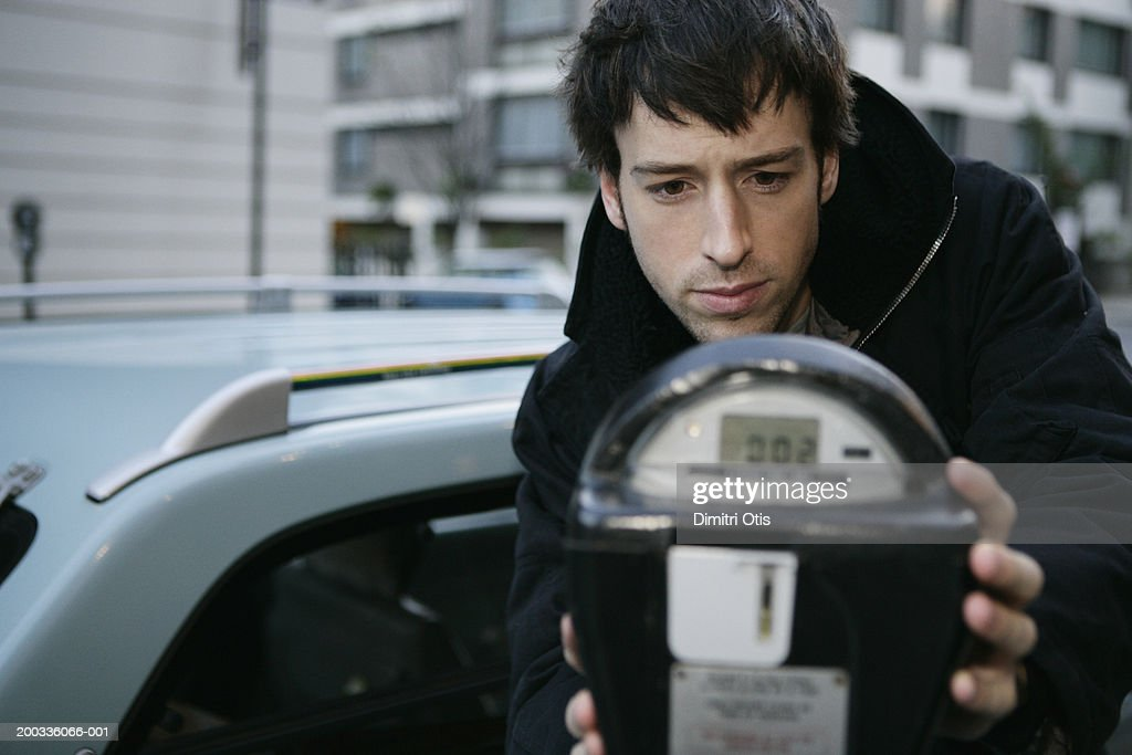 Man by parking meter outdoors