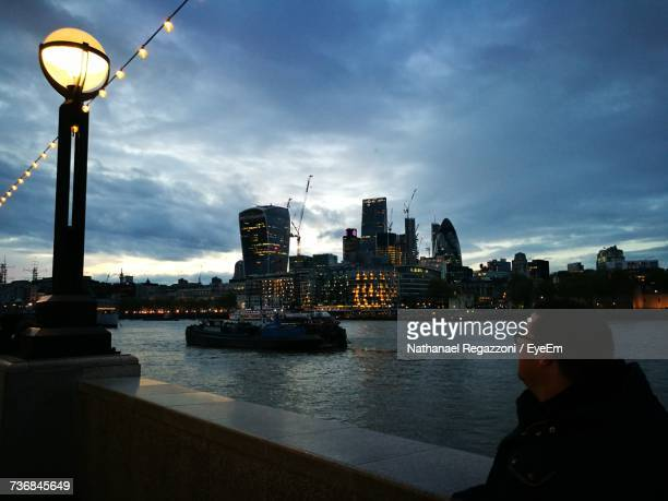Man By Thames River Looking At Skyscrapers In City Against Sky
