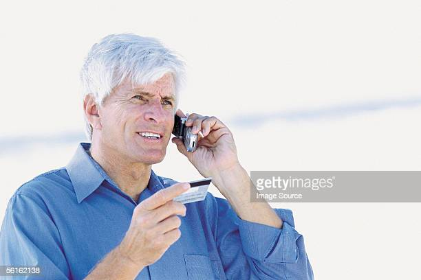 Man by the sea with cellphone and credit card