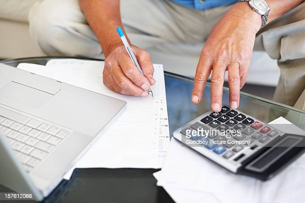 Man calculating budget with laptop and calculator