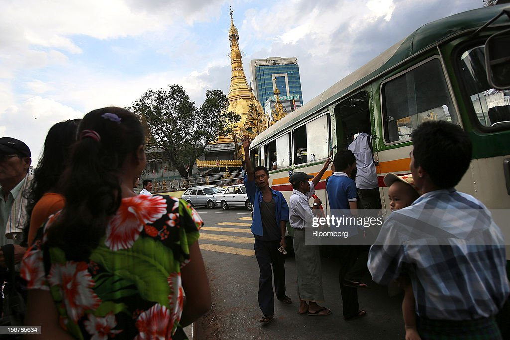 A man calls for passengers at a bus station near Sule Pagoda in Yangon, Myanmar, on Tuesday, Nov. 20, 2012. Myanmar's growth outlook has improved 'substantially' amid political reforms, which are expected to lead to a large influx of foreign investment, the Organization for Economic Cooperation and Development (OECD) said on Nov. 18. Photographer: Dario Pignatelli/Bloomberg via Getty Images