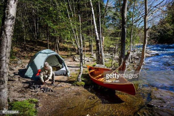 Man camping at the riverbank with a canoe