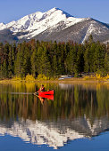 Man Canoeing and Fly Fishing On Colorado Lake