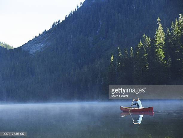 Man canoeing on lake cover with fog, rear view