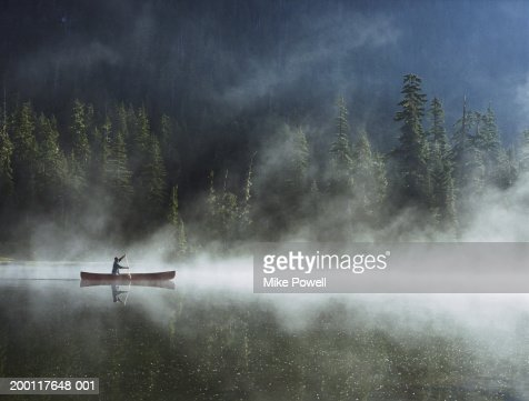 Man canoeing on lake cover with fog, side view : Stock Photo