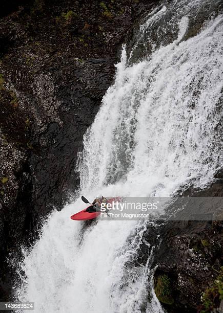 Hombre piragüismo en rocky cascada