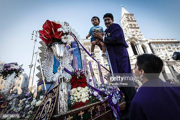 A man carries a baby close to the image of the 'Lord of Miracles' or 'Senor de los Milagros' as he participates in Rome in a procession honoring...