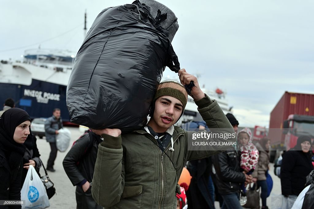 A man carries a bag as migrants and refugees walk in the port of Piraeus upon their arrival from the island of Lesbos on February 10, 2016. EU migration commissioner Dimitris Avramopoulos said on February 10, 2016 he has written letters to member states with a 'clear and strong message' to accelerate the relocation of refugees from overstretched Greece and Italy. Streams of people fleeing conflict or poverty continue to make the often perilous journey from Turkey across the Mediterranean and through the Balkans, despite cold winter weather, in the hope of starting new lives in more prosperous European countries. / AFP / LOUISA GOULIAMAKI