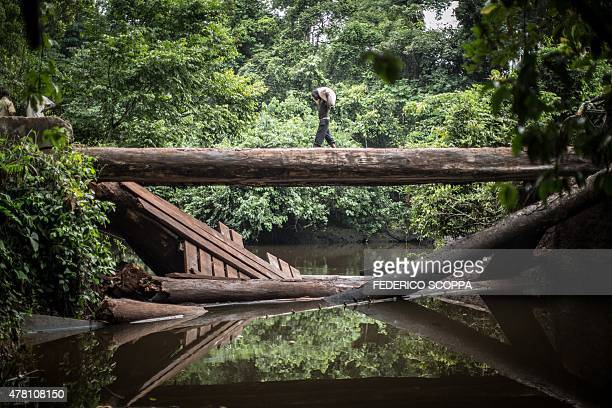 A man carries a bag of flour on a broken bridge on the road between Zongo and Libenge in the northwestern region of Democratic Republic of Congo on...