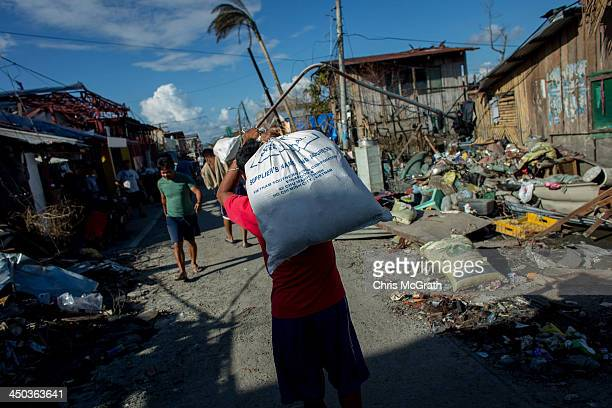 A man carries a bag of food aid to a distribution center on November 18 2013 in Leyte Philippines Typhoon Haiyan which ripped through the Philippines...