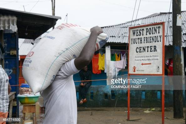 A man carries a bag of rice during a World Food Programme food distribution in Monrovia's West Point slum on September 6 2014 The death toll from the...