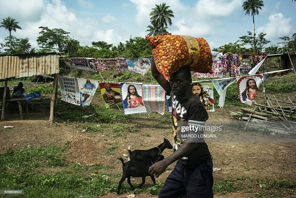 A man carries a bag of small peppers as he walks through stalls at a roadside market outside the northern Liberian town of Voinjama in Lofa county on April 28, 2016 / AFP / MARCO