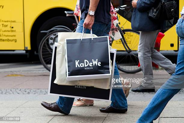 A man carries a bag of the brand KaDeWe during the endofsummer sales on August 19 2011 in Berlin Germany Growth in the German economy which is...