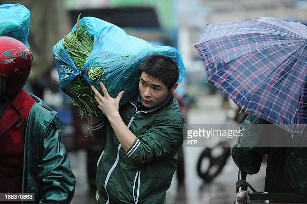 A man carries a bag of vegetables in the rain in Hefei east China's Anhui province on May 9 2013 Inflation in China accelerated to 24 percent...