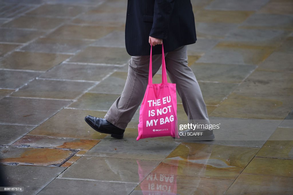 A man carries a bag with a message outside the Manchester Central convention centre, in Manchester on October 1, 2017, the first day of the Conservative Party annual conference. British Prime Minister Theresa May's Conservative Party gathers on October 1, 2017, for its annual conference, dominated by questions about her leadership and splits on Brexit. / AFP PHOTO / Oli SCARFF