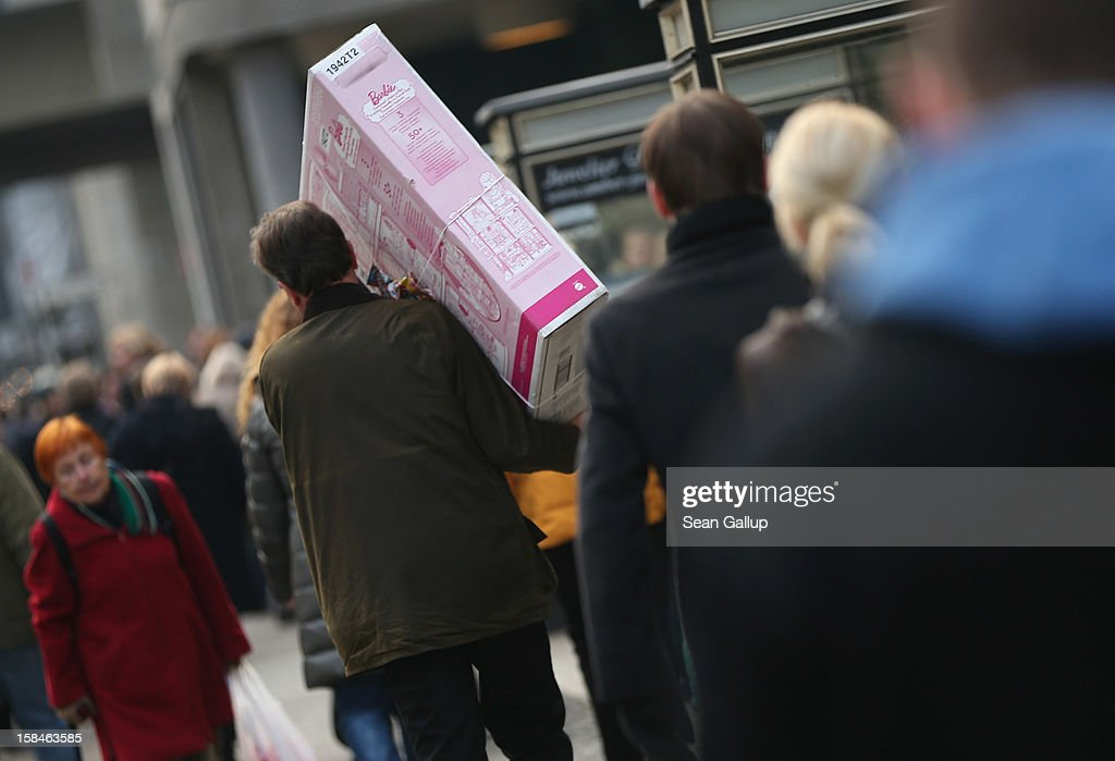 A man carries a Barbie playset on a busy shopping street in Steglitz district on December 17, 2012 in Berlin, Germany. Retailers are hoping for a strong Christmas season in Germany, one of the few countries whose economy has so far weathered the current Eurozone debt crisis relatively well.