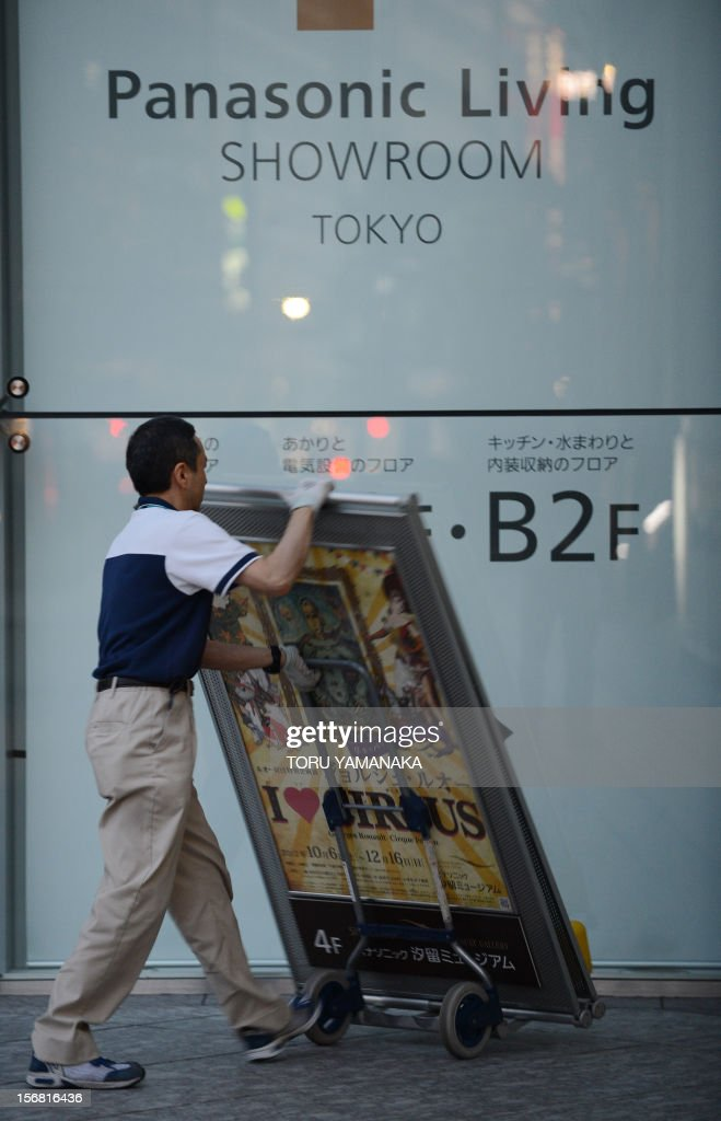 A man carries a billboard under a logo of Japan's Panasonic at its head office in Tokyo on November 22, 2012. Fitch on November 22 dealt another blow to the Japan's embattled electronics sector, cutting its credit rating on industry titans Panasonic and Sony to junk status. AFP PHOTO/Toru YAMANAKA