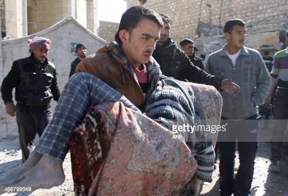 A man carries a body following a reported Syrian government forces air strike in the northern city of Aleppo on February 4 2014 Syrian army...