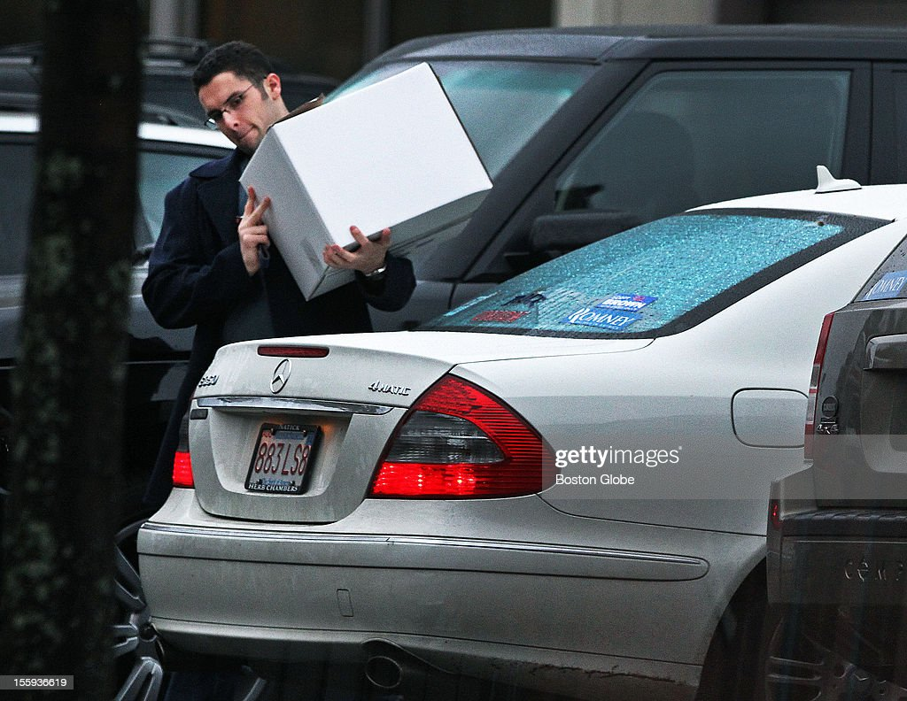 A man carries a box that he is about to put into the trunk of a car with a 'Romney' sticker on the back windshield that he carried out of the Romney headquarters on Commercial Street in Boston late on Thursday afternoon.