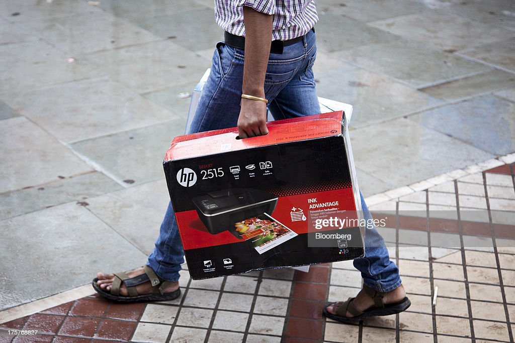 A man carries a boxed Hewlett-Packard Co. 2515 printer in Nehru Place IT Market, a hub for the sale of electronic goods and computer accessories, in downtown New Delhi, India on Wednesday Aug. 7, 2013. India's consumer price index (CPI) figures for July are scheduled to be released on August 12. Photographer : Graham Crouch/Bloomberg via Getty Images